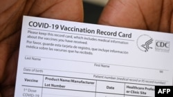 A healthcare worker displays a Covid-19 Vaccination Record Card at QueensCare Health Center in Los Angeles, California, Aug. 11, 2021.