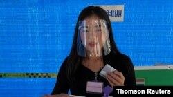 ស្ត្រីម្នាក់ពាក់របាំងការពារមុខទៅបោះឆ្នោតនៅក្នុងការបោះឆ្នោតថ្នាក់ខេត្ត នៅខេត្ត Nonthaburi ប្រទេសថៃ ថ្ងៃទី២០ ខែធ្នូ ឆ្នាំ២០២០។