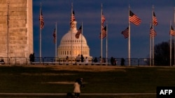 WASHINGTON, DC - DECEMBER 26: The US Capitol Building is seen past the Washington Monument as the sun sets on December 26, 2020 in Washington, DC. Lawmakers in Congress are continuing to work on the coronavirus relief package following President…