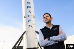 Jared Isaacman, pendiri dan CEO Shift4 Payments, berdiri di depan potret roket Falcon 9 tahap pertama di Space Exploration Technologies Corp. (SpaceX), 2 Februari 2021. (Patrick T. FALLON / AFP)