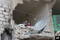 FILE - Children peer from a badly damaged home in Aleppo, Syria, Feb. 11, 2016.