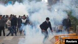 Para pengunjukrasa berlindung dari gas air mata yang ditembakkan oleh polisi selama protes terhadap RUU Amendemen Kewarganegaraan, New Delhi, 13 Desember 2019. (Foto: Reuters)