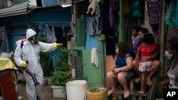Seorang pekerja bersiap menyemprotkan cairan disinfektan di pemukiman kumuh di Santa Marta, Rio de Janeiro, Brazil, 10 April 2020.