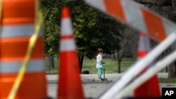 A child rides a scooter past barricades at an entrance to Tower Grove Park in St. Louis, Missouri, March 31, 2020.