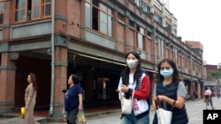 People wearing face masks to help curb the spread of the coronavirus walk on a street in Taipei, Taiwan, Monday, Oct. 19, 2020. (AP Photo/Chiang Ying-ying)