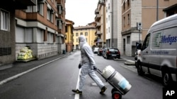 A staffer delivers a medical oxygen tank to coronavirus patients who are being treated at home, in Bergamo, one of the areas worst affected by the virus, Northern Italy, Tuesday, March 31, 2020. The new coronavirus causes mild or moderate symptoms…