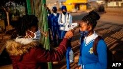 Seorang petugas mengukur suhu tubuh seorang murid SMP Winnie Mandela sebelum masuk ke kelasmya di kota Tembisa, Ekurhuleni, Afrika Selatan, 8 Juni 2020. (Foto: dok).