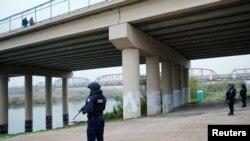 Petugas polisi federal Meksiko berdiri di tepi Rio Bravo dekat jembatan yang menghubungkan Eagle Pass, Texas, dengan Piedras Negras, di Piedras Negras, Meksiko, 10 Februari 2019. (Foto: Reuters)