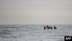 Migranti u čamcu plove preko nemirnih voda Engleskog kanala, pored severne Francuske, u pokušaju da se dokopaju obala Britanije. (Fotografija godine 2020, AFP)