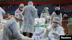 Volonteri pomažu da se spakuju kutije s pomoći za starije građane Beograda, kojima je zabranjeno da izađu napolje zbog epidemije koronavirusa (Foto: Reuters/Feđa Grulović)