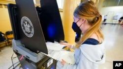 ARHIVA - Džun Harkrajder, koja je napunila 18 godina u martu, stavlja svoj glasački listić u skener dok po prvi put glasa na stranačkim izborima u gradu Njujorku, 14. juna 2021.