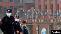 FILE - Security personnel keep watch outside the Wuhan Institute of Virology during the visit by the World Health Organization (WHO) team tasked with investigating the origins of the coronavirus disease, inWuhan, Hubei province, China, Feb. 3, 2021.