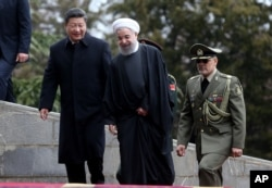 FILE - Chinese President Xi Jinping, left, is welcomed by Iranian President Hassan Rouhani during his official arrival ceremony at the Saadabad Palace in Tehran, Iran, Jan. 23, 2016.