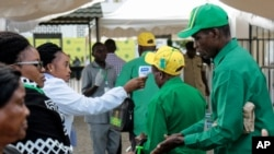FILE - Party members have their temperature checked and sanitize their hands as a precaution against the coronavirus at the national congress of the ruling Chama cha Mapinduzi (CCM) party in Dodoma, Tanzania, July 11, 2020.