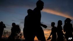Silueta de personas que camina por el cerro El Volcán durante la puesta de sol en El Hatillo de Caracas, el 25 de abril de 2021.