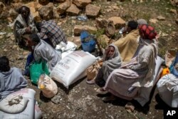FILE - An elderly Ethiopian woman sits next to a sack of wheat given to her by the Relief Society of Tigray in the town of Agula, in the Tigray region of northern Ethiopia, May 8, 2021.