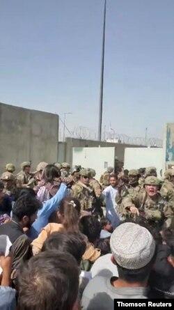 Tentara Afghanistan mencoba untuk membubarkan kerumunan di luar bandara Kabul. (REUTERS)