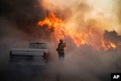 FILE - Firefighter Raymond Vasquez battles the Silverado Fire, in Irvine, Calif., Oct. 26, 2020.