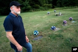 FILE - Eddie Davis stands beside the grave of his son Jeremy, furthest left, who died from the abuse of opioids at the age of 35, July 17, 2019, in Coalton, Ohio.