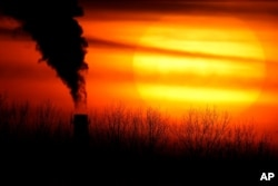 Emissions from a coal-fired power plant are silhouetted in Independence, Missouri, Feb. 1, 2021.