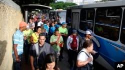 Para calon penumpang berdiri di jalur bus di Caracas, Venezuela, Selasa, 23 Juli 2019. Lampu kembali menyala di seluruh Venezuela Selasa pagi (23/7), menyusul pemadaman besar sehari sebelumnya yang melumpuhkan komunikasi di kota Caracas.