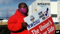 2月9日在亞馬遜貝塞默倉庫前,工會成員佛斯特舉牌呼籲工人投票同意加入工會(美聯社)