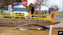 A piece of debris from a commercial airplane is marked off by police tape where it landed along Midway Boulevard in Broomfield, Colo., as the plane shed parts while making an emergency landing at nearby Denver International Airport, Feb. 20, 2021.