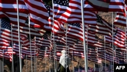 FILE - A young woman wearing a hijab stands amongst U.S. national flags erected by students and staff from Pepperdine University to honor the victims of the Sept. 11, 2001, attacks, at their campus in Malibu, California, Sept. 10, 2016.