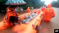 This photograph provided by India's National Disaster Response Force (NDRF) shows NDRF personnel carrying food boxes for residents in Chiplun area in the western Indian state of Maharashtra, July 23, 2021.