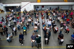 FILE - People wait to receive the first dose of China's Sinovac Biotech CoronaVac vaccine against COVID-19, in Ecatepec, Mexico state, Feb. 22, 2021.