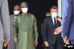 Burkina Faso President Roch Marc Christian Kabore, left, Chad President Idriss Deby, center, and France President Emmanuel Macron arrive for a picture during the G5 Sahel summit on June 30, 2020, in Nouakchott, Mauritania.