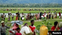 FILE - Rohingya refugees, who crossed the border from Myanmar, walk toward refugee camps, in Palang Khali, near Cox's Bazar, Bangladesh, Oct. 19, 2017.