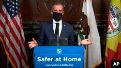 Мер Лос Анджелеса на прес-конференції демонструє, як носити захисну маску. 1 квітня 2020 р.