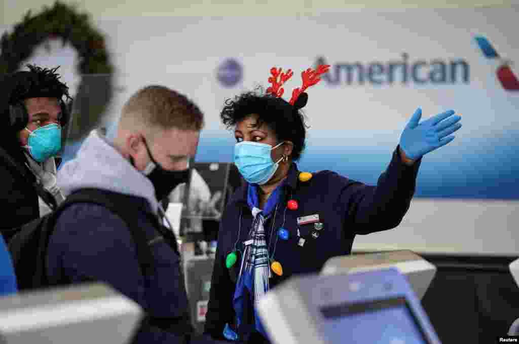 Un trabajador de una aerolínea con atuendo temático de Navidad ayuda a los viajeros en el Aeropuerto Nacional Ronald Reagan de Washington en Arlington, Virginia, EE. UU., 22 de diciembre de 2020.