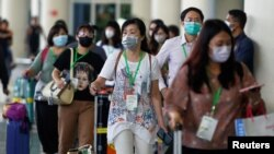Passengers wearing medical masks walk as they arrive at international arrival terminal of I Gusti Ngurah Rai airport following an outbreak of the new coronavirus in China, in Bali, Indonesia, February 4, 2020. Picture taken February 4, 2020. REUTERS…