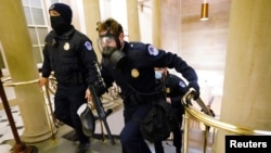 U.S. Capitol police officers take positions as protestors enter the Capitol building during a joint session of Congress to certify the 2020 election results on Capitol Hill in Washington, Jan. 6, 2021.
