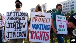 Demonstrators hold signs during a march for voting rights, marking the 58th anniversary of the March on Washington, Aug. 28, 2021, in Washington.