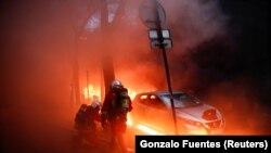 Des pompiers à côté d'une voiture entourée de flammes lors d'une manifestation contre un projet de loi controversé, à Paris, France, le 5 décembre 2020.