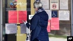 زنی در مقابل اداره کار ایالت ایلینوی به تقاضاهای کار نگاه می کند. آرشیو، ۹ آوریل ۲۰۲۰