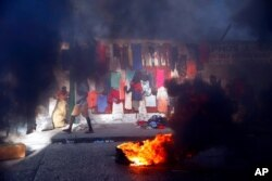 FILE - Smoke from tires set fire by protesters fills a street in Delmas where vendors sell clothing during a countrywide strike demanding the resignation of Haitian President Jovenel Moise in Port-au-Prince, Haiti, Feb. 1, 2021.