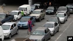 Vehículos hacen fila cerca de una estación de servicio para llenar sus tanques, en Caracas, Venezuela. El precio internacional fue establecido en 0.50 centavos de dólar por litro.