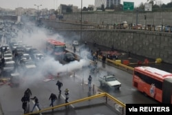 FILE - Riot police try to disperse protesters as they rally on a highway against increased fuel prices, in Tehran, Iran, Nov. 16, 2019.
