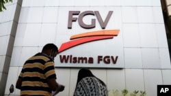 """A couple talks outside FGV Holdings Berhad, one of Malaysia's largest palm oil companies, in Kuala Lumpur, Thursday, Oct. 1, 2020. Malaysian palm oil producer FGV Holdings Berhad vowed Thursday to """"clear its name"""" after the U.S. banned imports of…"""