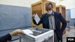 یک مرد الجزایری با شرکت در همه پرسی تغییر قانون اساسی رای خود را در یک حوزه اخذ رای در پایتخت الجزایر به صندوق می اندازد. ۱ نوامبر ۲۰۲۰