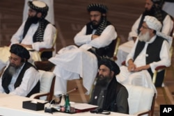 FILE - Taliban co-founder Mullah Abdul Ghani Baradar, bottom right, speaks at the opening session of the peace talks between the Afghan government and the Taliban in Doha, Qatar, Sept. 12, 2020.