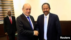 Perdana Menteri Sudan Abdalla Hamdok berjabat tangan dengan Menteri Luar Negeri Prancis Jean-Yves Le Drian selama pertemuan mereka di Khartoum, Sudan, 16 September 2019. (Foto: Reuters)