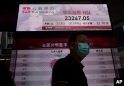 A man wearing face mask walks past a bank's electronic board showing the Hong Kong share index at Hong Kong Stock Exchange, Sept. 28, 2020.