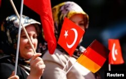 A Turkish woman waves a Turkish and a German flag during a demonstration including members of the Turkish ultra-nationalist organization called the Grey Wolves in Duesseldorf, western Germany, May 8, 2016.