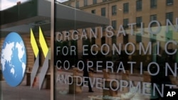 The logo at the entrance of the Organisation for Economic Co-operation and Development (OECD) headquarters in Paris, France, Wednesday, June 7, 2017. (AP Photo/Francois Mori)