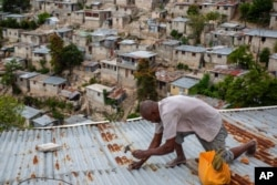Antony Exilien secures the roof of his house in response to Tropical Storm Elsa, in Port-au-Prince, Haiti, July 3, 2021.